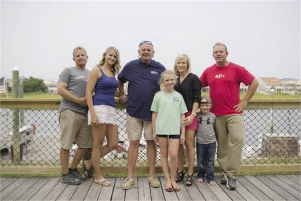 A family standing on a dock or pier.
